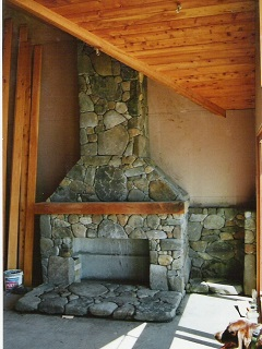 Stone Boulder Fireplace with Wooden Mantlepiece